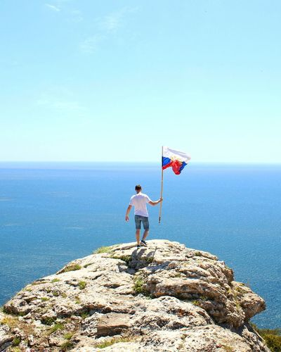 Rear View Of Man With Flag On Cliff Against Sea During Sunny Day