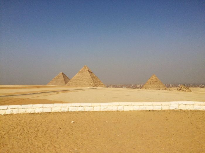 Distant view of great pyramid of giza against clear sky