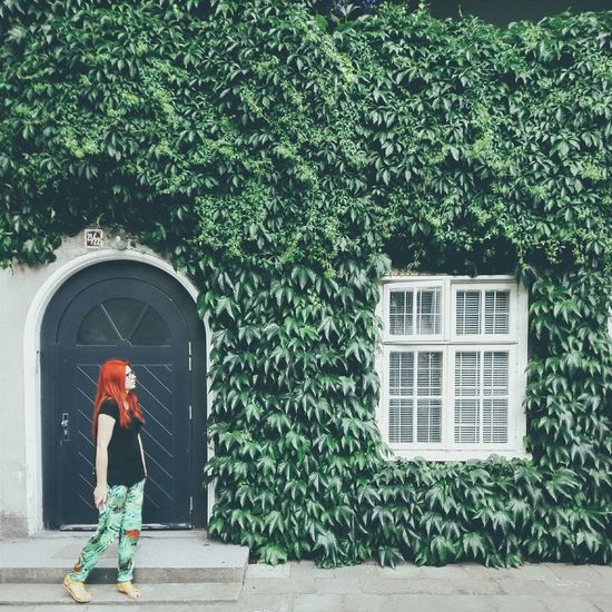 Full length of woman standing against house covered with ivy leaves