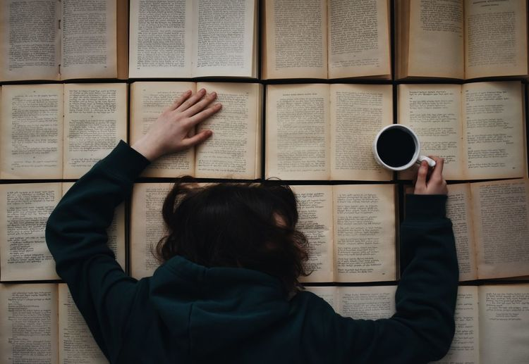 Directly Above Shot Of Woman Having Coffee While Leaning On Books