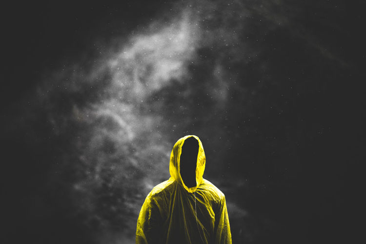 Silhouette man wearing yellow raincoat standing against black background