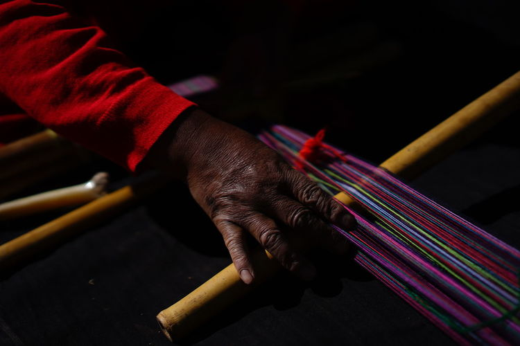 Close-up of man working on loom