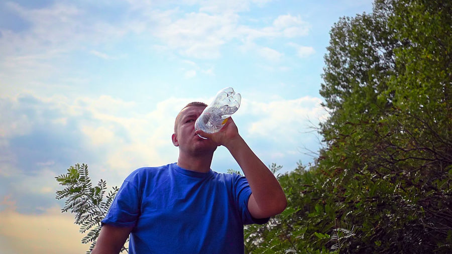 Man is drinking fresh water from a plastic bottle Athletic Man Nature Picnic Plastic Bottle Summertime Thirst Thirsty  Authentic Candid Drink Drinking Fresh Water Handsome Male Outdoors Real People Sky Sportive Strong Strong Man Summer Sunset Water The Traveler - 2018 EyeEm Awards
