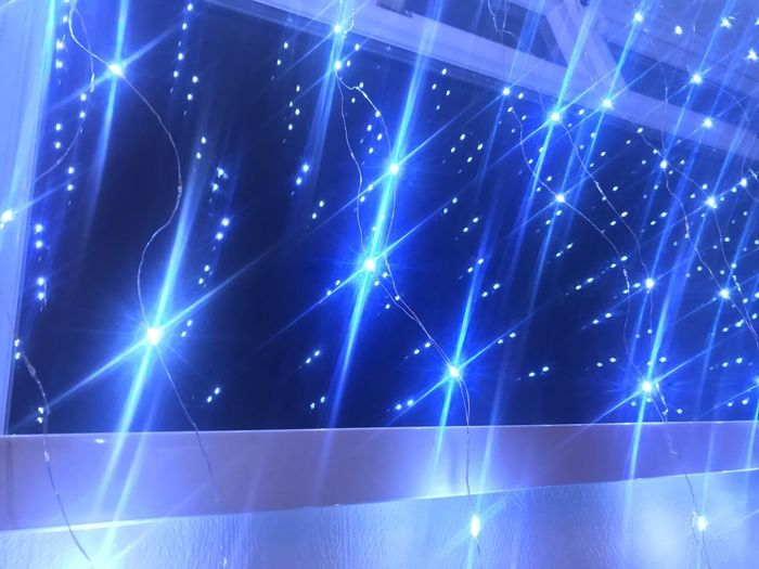 Low angle view of illuminated lights against blue sky at night