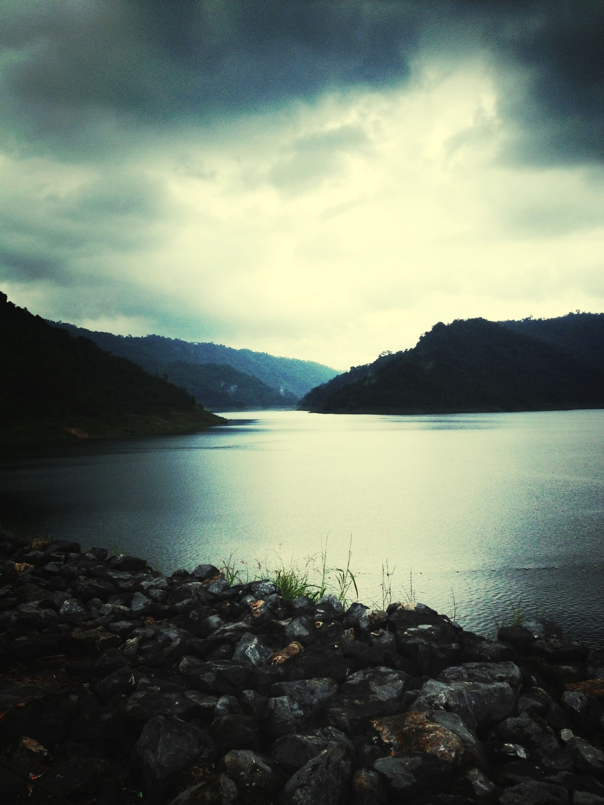 water, mountain, tranquil scene, sky, tranquility, scenics, beauty in nature, cloud - sky, lake, rock - object, nature, mountain range, cloudy, cloud, idyllic, landscape, non-urban scene, river, stone - object, outdoors