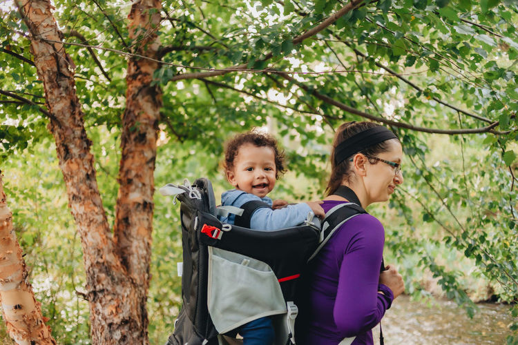 Smiling mother with cute son on back standing on forest
