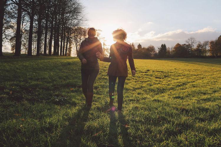 Friends Walking On Grassy Field At Park