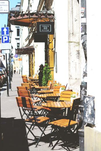 Chairs and tables at sidewalk cafe in city