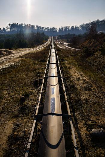 Metal bridge over field against sky