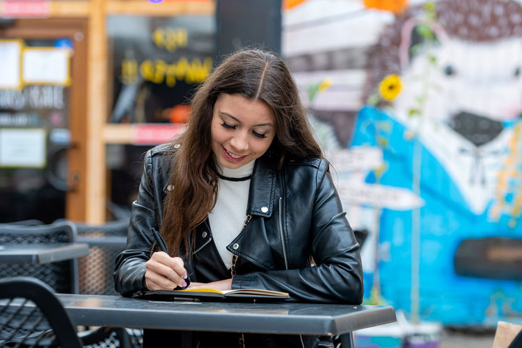 Smiling woman writing in diary while sitting at cafe