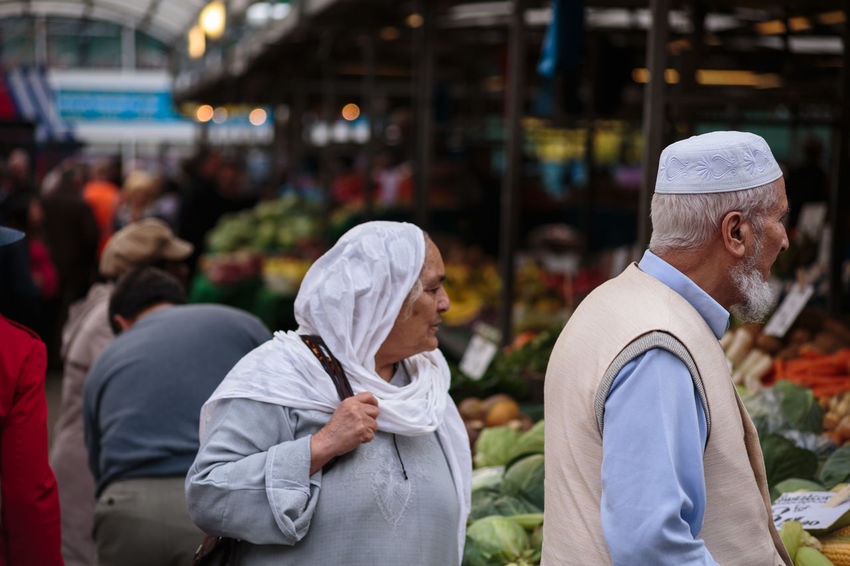 Muslim couple walking through food market Muslim Couple Two People Blurred Background Shallow Depth Of Field Full Frame Unprocessed No Filter Horizontal Eye Level Beard Unshaven Head Scarf Fruit And Vegetable Market Editorial  Outside Looking Sideways