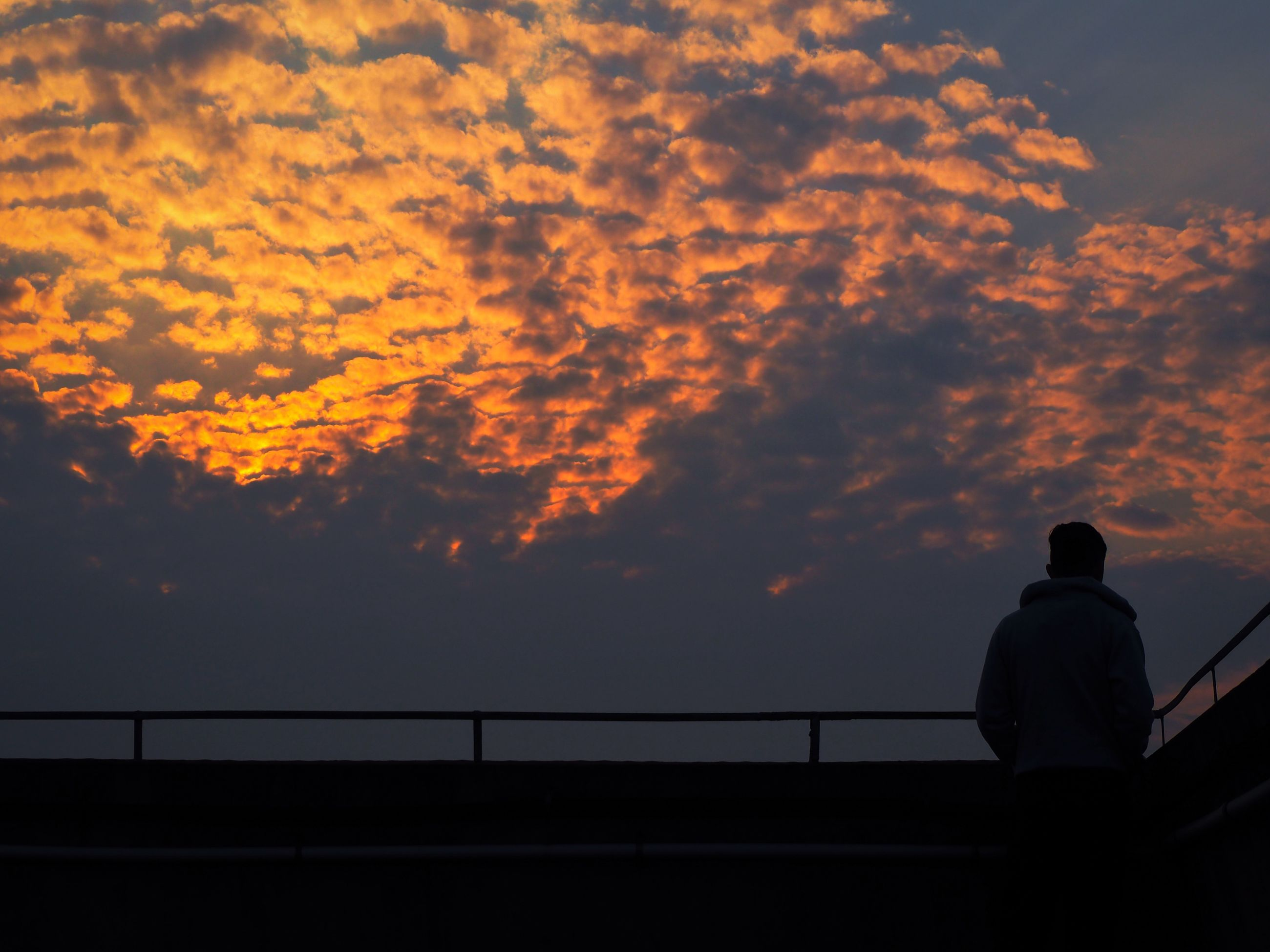 sunset, silhouette, sky, cloud - sky, orange color, railing, cloud, standing, cloudy, dramatic sky, men, scenics, beauty in nature, tranquility, lifestyles, nature, dusk, tranquil scene