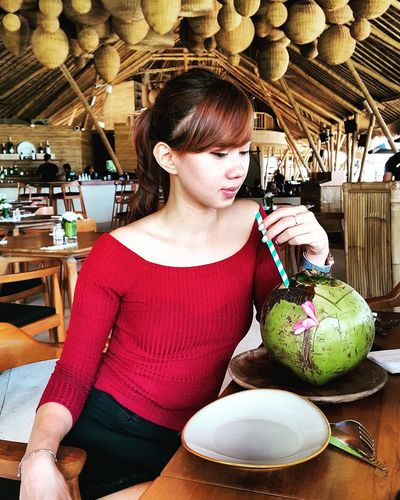 Young woman drinking coconut water in restaurant