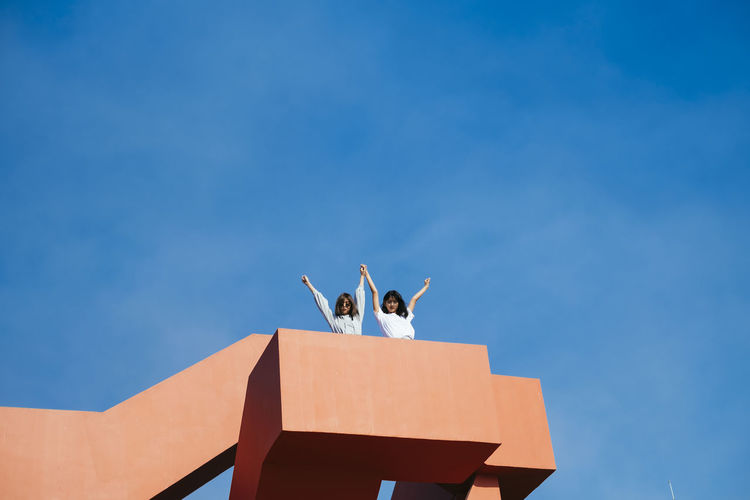 Low angle view of friends standing on terrace against sky