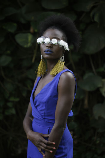 Woman wearing flowers over eyes while standing against plants