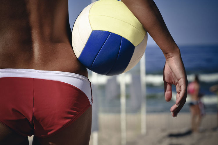 Midsection of woman holding ball at beach