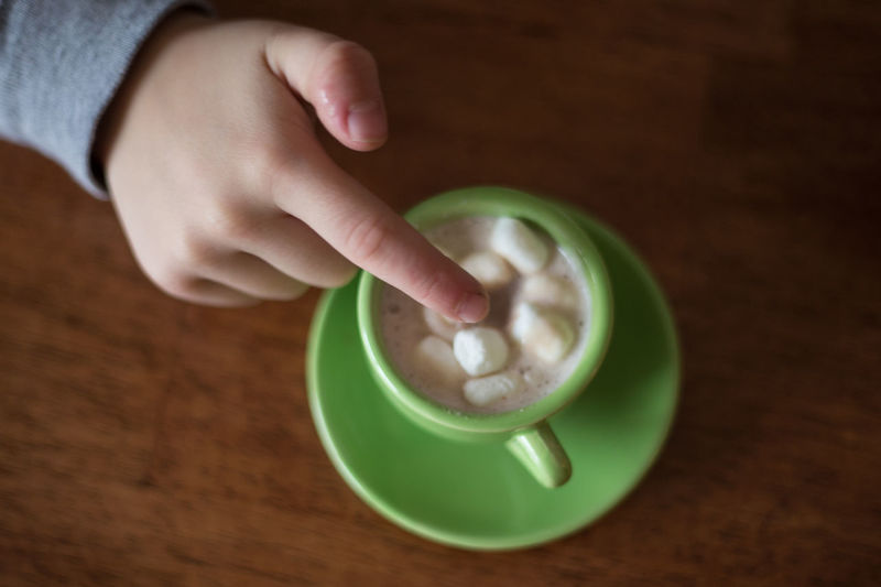 Cropped Hand Touching Sugar Cubes In Cup At Table