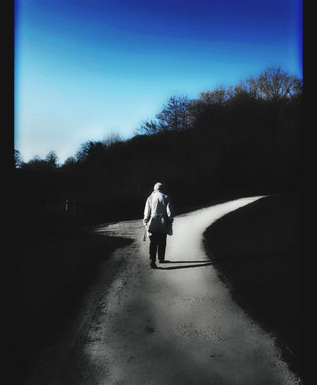 Walking into the future. The Way Forward The Road Ahead Rear View One Person Elderly Woman Real People Full Length Outdoors People Sky Day Adults Only Low Angle View Sunshine Day Sky And Clouds. Blue Sky Landscape One Person At A Time One Person Walking Long Goodbye