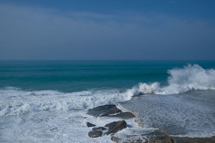 Scenic view of sea and waves against sky
