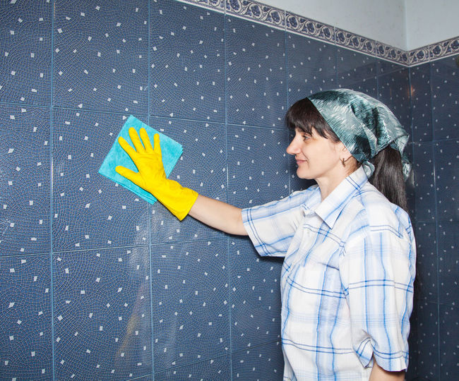 Woman cleaning tiled wall at home