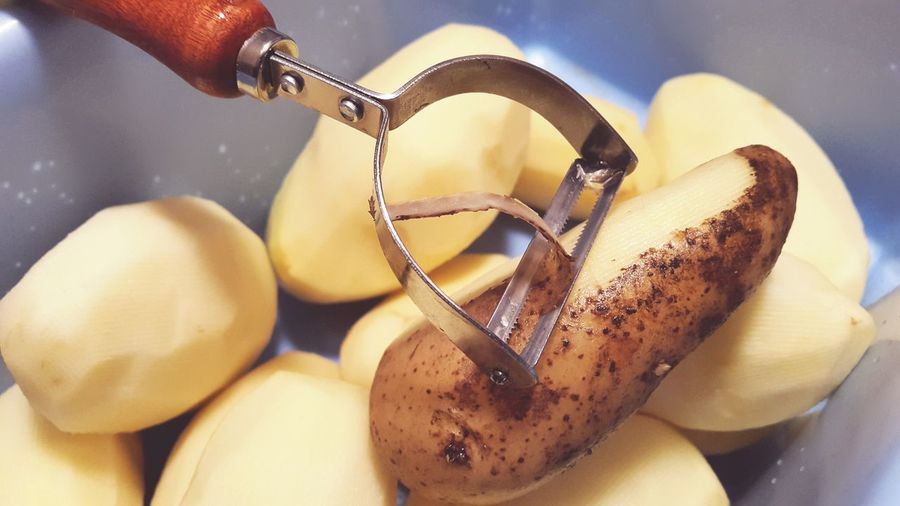High Angle View Of Potatoes And Peeler