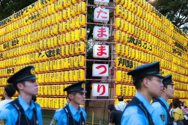 Policemen take car that everything is safe during the Mitama Matsuri festival in summer at the shinto shrine Yasukuni Jinja in Tokyo. Japan Japan Photography Japanese Culture Japanese Temple Lanterns Matsuri Mitama Matsuri Policeman Tokyo Adult Blue Festival Group Of People Hat Lifestyles Men Outdoors People Police Police Force Real People Street Streetphotography Yellow Yellow Color The Photojournalist - 2018 EyeEm Awards