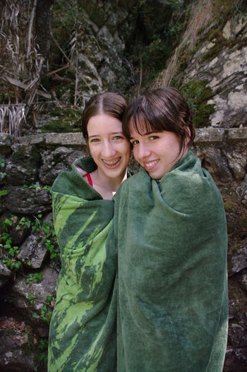 Portrait Of Female Friends Wrapped In Green Towel Against Rock Formations