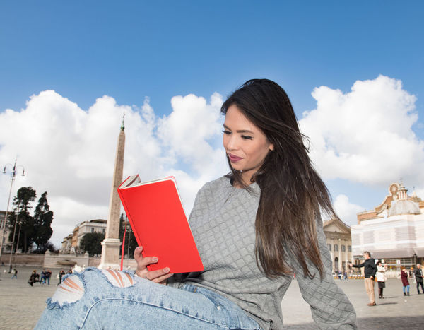 Young latina woman with red guidebook in piazza del popolo Architecture Reading Red Book Education Famous Place Guidebook Information One Young Woman Only Piazza Del Popolo Reading A Book Tourism Travel Destinations