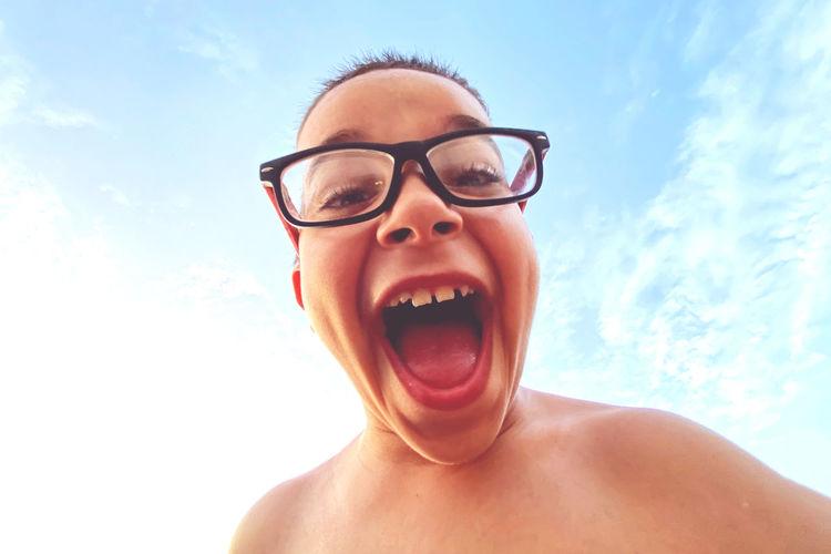 Portrait of shirtless man wearing eyeglasses against sky