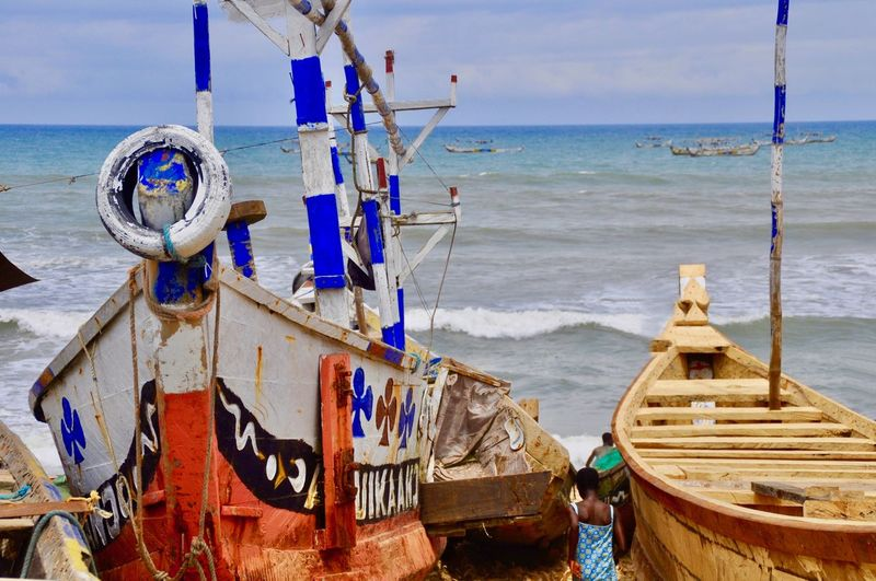 Fishing boats moored on beach against sky