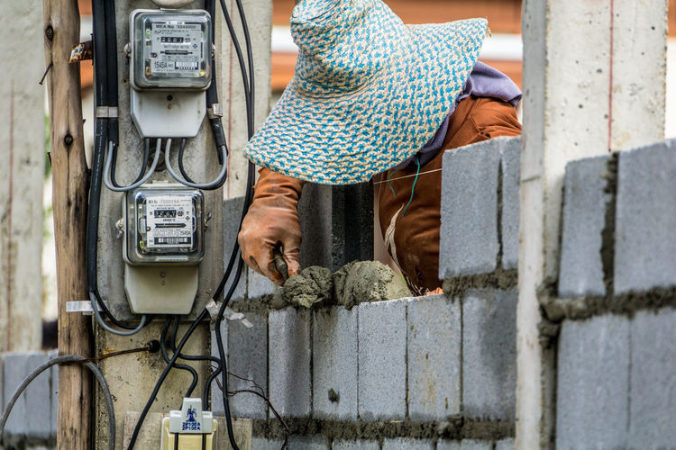 Manual worker wearing hat while working at construction site