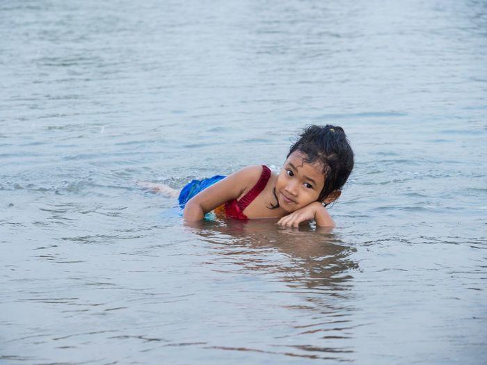 Portrait of girl lying in sea