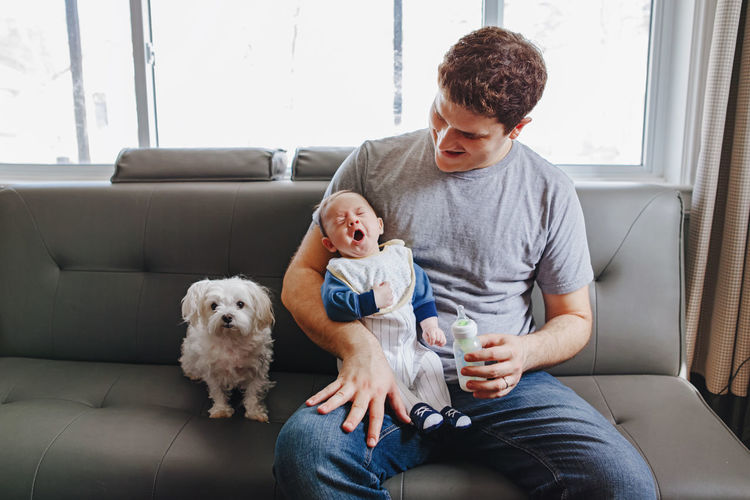 Man sitting with baby boy and dog on sofa in living room at home