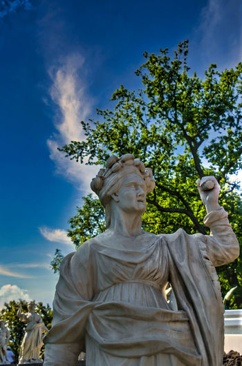 Low angle view of statue against trees and sky