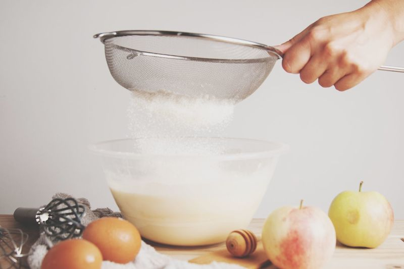 Cropped hand of person filtering flour using sieve in bowl at home