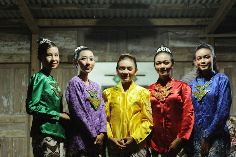Portrait of smiling women wearing colorful traditional clothing while standing against house at night