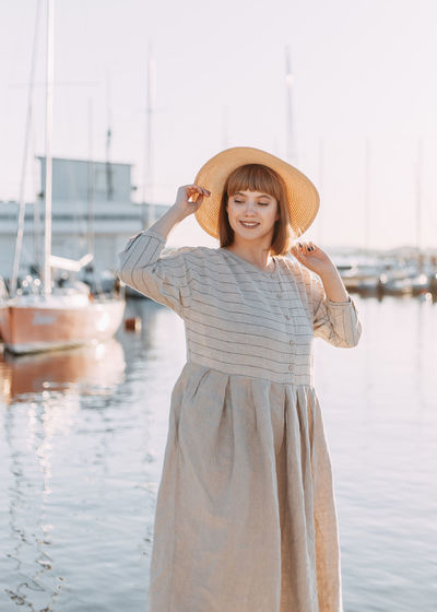 Happy young woman in dress and hat walks on the beach near the boats