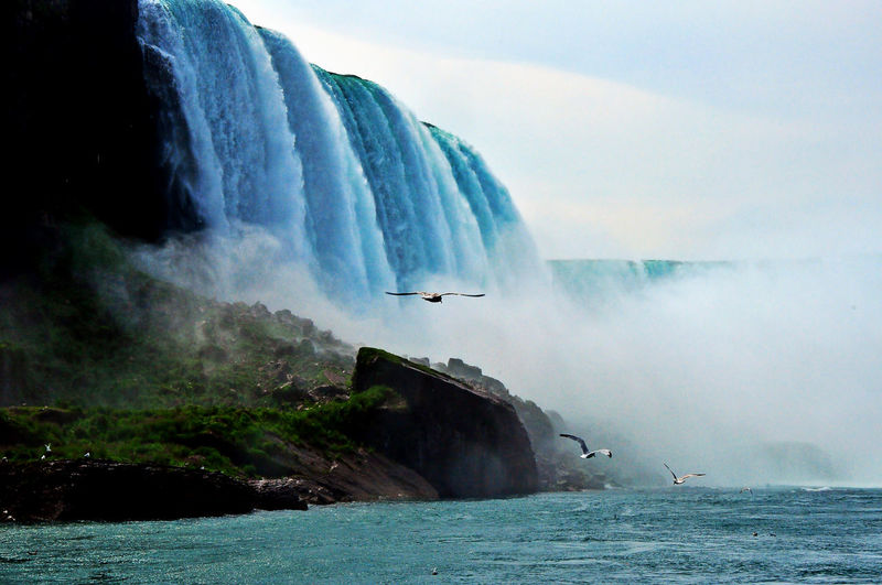 Scenic view of waterfall sea against sky