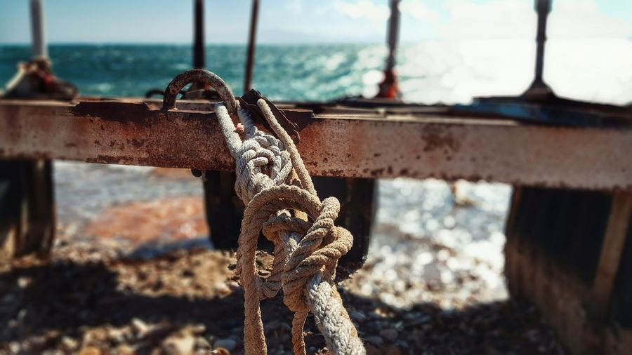 Close-Up Of Rope Tied On Metal At Beach