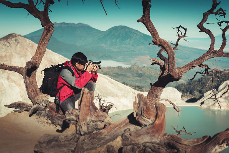 Portrait of traveler photography is shooting landscape picture at Kawah Ijen volcano, National Park of Indonesia.,Outdoor adventure traveling destination., Hobbies and leisure activities concept. Mountain Real People Tree Beauty In Nature Leisure Activity Lifestyles Nature Scenics - Nature People Plant Non-urban Scene Mountain Range Day Full Length Outdoors Photography Photographer Vacations Travel Kawah Ijen INDONESIA Volcano Volcanic Landscape Man Professional