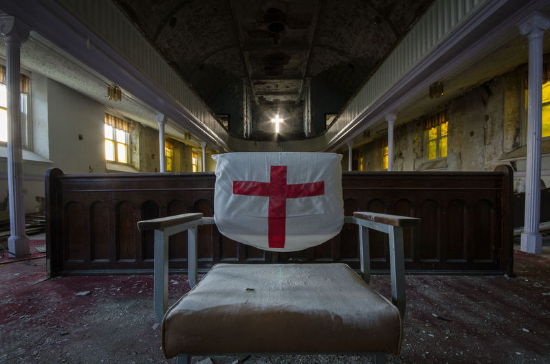 Cross sign on chair in abandoned church
