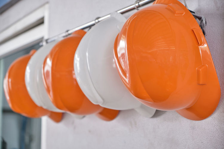 Close up hard hats hanging on hook against the dirty white wall.