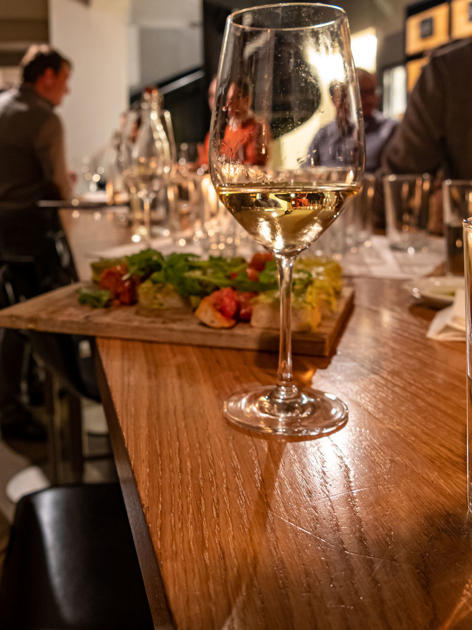 food and drink, table, wine, glass, drink, refreshment, food, alcohol, wineglass, business, freshness, indoors, focus on foreground, restaurant, incidental people, drinking glass, real people, glass - material, lifestyles, wood - material, red wine