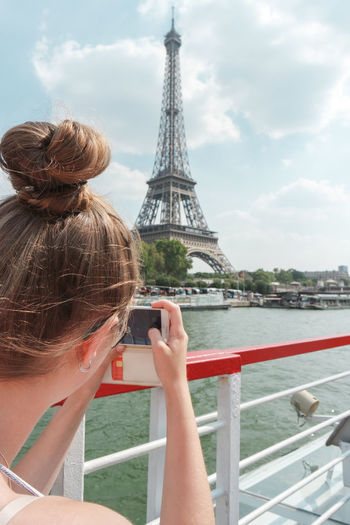Woman Photographing At Eiffel Tower Against Sky