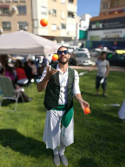 Full Length Of Young Man Wearing Sunglasses Juggling Balls While Standing On Grassy Field