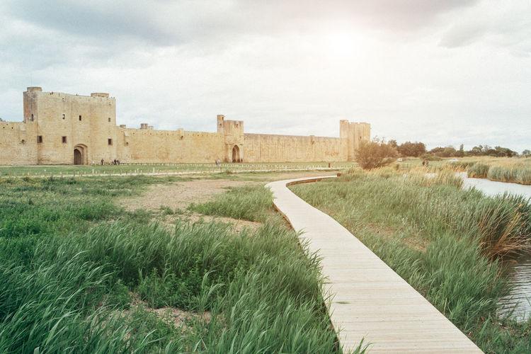 Boardwalk leading towards aigues-mortes fort against sky
