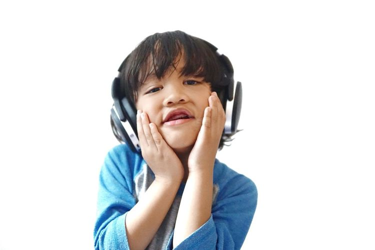 Cute boy listening music against white background