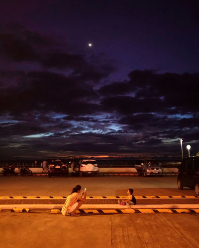 People sitting on shore against sky at night