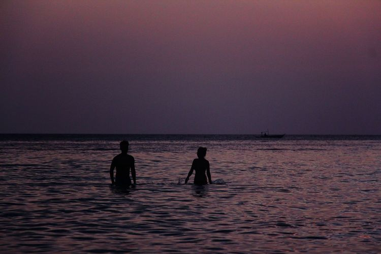 Silhouette Couple Enjoying In Sea Against Clear Sky During Sunset