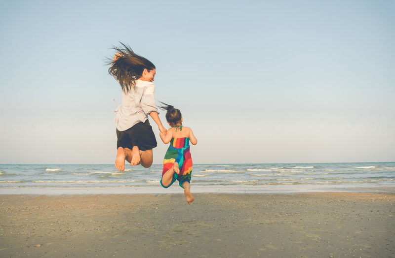Happiness Jumping Shot Beach Beauty In Nature Childhood Day Full Length Fun Girl Horizon Over Water Jumping Leisure Activity Lifestyles Mom Motion Nature Outdoors People Sand Sea Sky Two People Vacations Walking Water